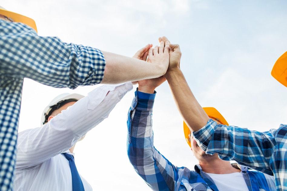 Handwerker halten ihre Hände hoch und zusammen